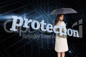 Businesswoman holding umbrella behind the word protection