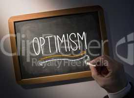 Hand writing Optimism on chalkboard