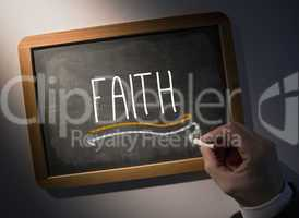 Hand writing Faith on chalkboard