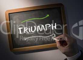 Hand writing Triumph on chalkboard