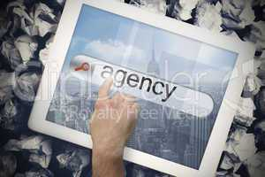 Hand touching agency on search bar on tablet screen