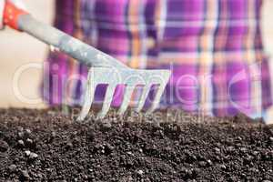 woman works with rake their humus soil