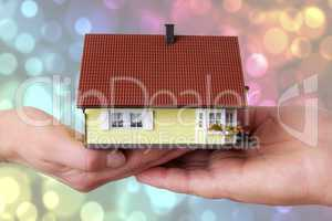 hands of woman and man holding model house