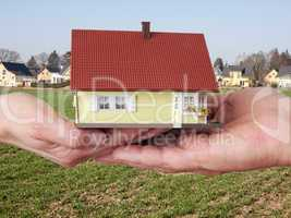 hand holding model house on the building site