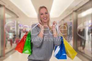 lachende blondine beim einkaufen in shopping mall