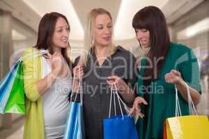 gruppe junger frauen schaut auf die einkäufe in shopping mall