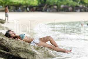 woman lying on rocky beach