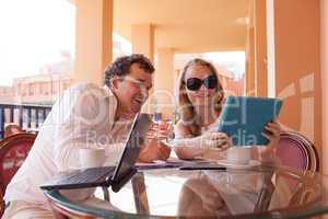 young couple relaxing over coffee on a balcony
