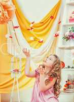 Beautiful curly-haired girl plays with petals