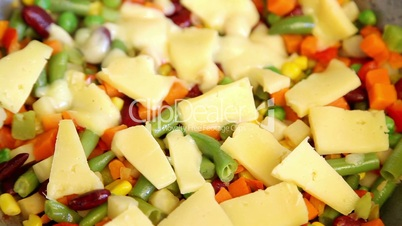 melting cheese on vegetable mix