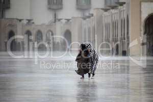 Two Moroccans run through the rain