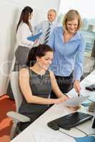 businesswomen discussing document