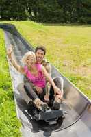 happy couple enjoying summer sledge