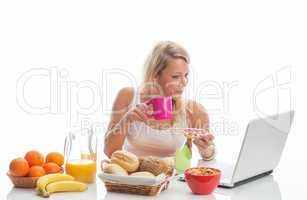 frau beim frühstück mit laptop