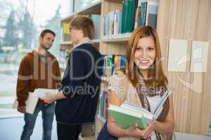college student holding books in library