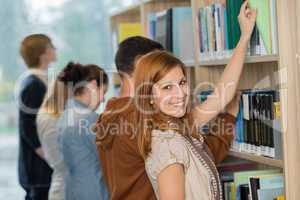 student choosing book from bookshelf in library