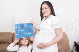 girl holding a 30 weeks sign to her expectant mother