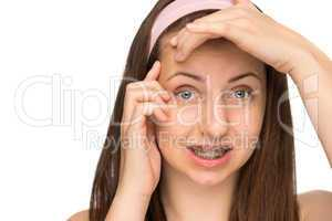 worried girl with braces squeezing pimple isolated