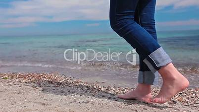 slim girl in jeans goes barefoot on the beach