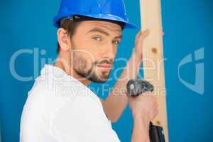 Builder using a drill looking at the camera