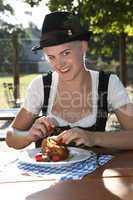 Blonde girl eats half chicken in a traditional beer garden