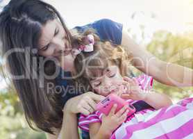 Mother and Cute Baby Daughter Playing with Cell Phone