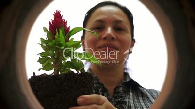 female gardener inside clay pot planting