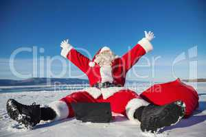 Santa Claus sitting on snow glad news in the laptop