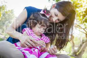 Young Mother and Cute Baby Girl Applying Fingernail Polish