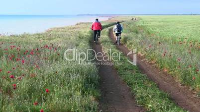 Adult couple riding bicycles along the seashore down a dirt road