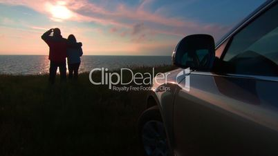 Couple near his car on sea coast watching the sunset