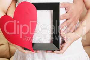 hands embracing a pregnant woman belly with her hands holding a