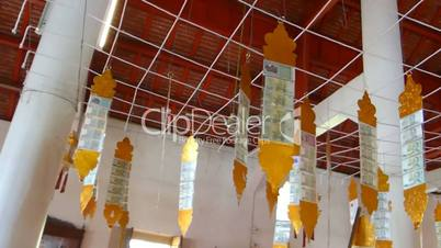 Temple donation money hanging on metal trilles in a Thai temple(CM--3a