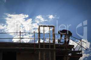 Construction Worker Silhouette on Roof