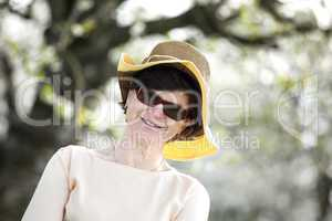 Women portrait with straw hat under blooming cherry tree old