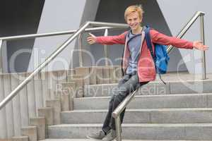 Playful student sliding down handrail on stairway