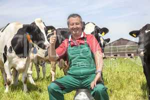 Farmer sitting on the milk jug in front of his cows