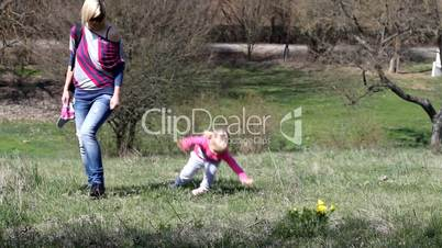 Mom and daughter in a field with yellow flowers