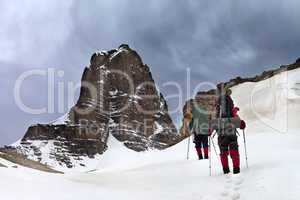 Two hikers in snowy mountains and storm sky