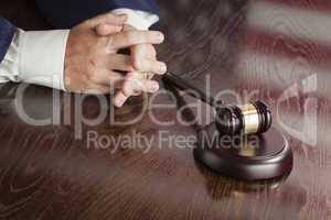 Judge Rests Hands Behind Gavel with American Flag Table Reflecti