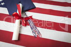Graduation Cap and Diploma Resting on American Flag