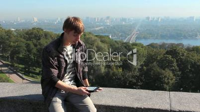 Young Man Reads Electronic Book At Kiev