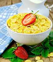 Cornflakes in bowl with strawberries on board
