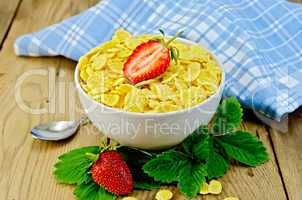 Cornflakes in white bowl with strawberries on board