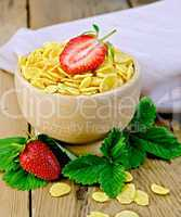 Cornflakes in wooden bowl with strawberries on board