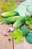 Cucumbers with jar and garlic on board