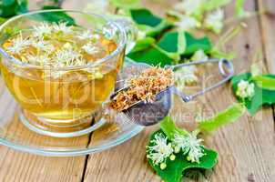 Herbal tea from linden flowers with strainer on board