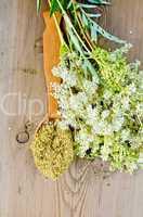 Herbal tea from meadowsweet in spoon on board