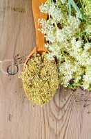 Herbal tea from meadowsweet in wooden spoon
