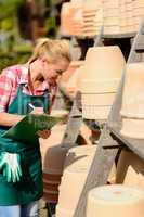 garden center woman write notes clay pots